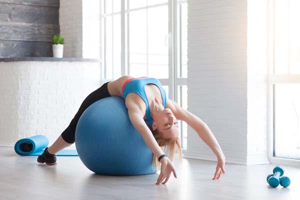 женщина в спортивной одежде на синем фитболе